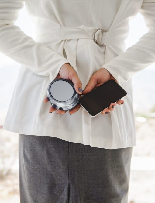 Business woman holding Skysurfer and phone behind her back